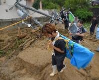 土砂崩れが発生した地域で、無傷の家電製品などを運び出す人たち=広島県熊野町で2018年7月8日午後5時39分、手塚耕一郎撮影