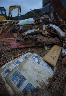 土砂崩れで行方不明者の捜索が続く現場。がれきが積み上がった片隅に写真アルバムが残されていた=広島県熊野町で2018年7月8日午後7時20分、手塚耕一郎撮影