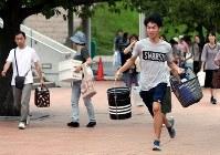 給水所を目指して駆ける男性(右)=広島県呉市で2018年7月8日午後4時25分、幾島健太郎撮影