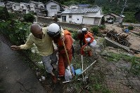 An elderly person is rescued from a home after a road was cut off by heavy rain, isolating people, in Kure, Hiroshima Prefecture, on July 8, 2018. (Mainichi)