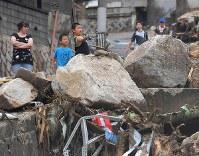 Children play near an area where huge rocks were left by a landslide, in Hiroshima's Aki Ward on July 8, 2018. (Mainichi)