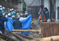 People look on with solemn expressions as a person is carried away from the scene where a home collapsed in a landslide, in Hiroshima's Aki Ward on July 8, 2018. (Mainichi)