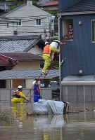 A woman is rescued from the second floor of a home in Kure, Hiroshima Prefecture, on July 8, 2018. (Mainichi)