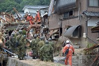 Rescue workers and Self-Defense Forces members examine a home that collapsed in a landslide, in Kure, Hiroshima Prefecture, on July 8, 2018. (Mainichi)