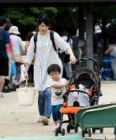 A young boy pushes distributed water on a stroller in the wake of torrential rain in Kure, Hiroshima Prefecture, on July 8, 2018. (Mainichi)