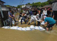 People pile up sandbags against a river overflowing into a residential area, where they say water levels are higher than the day before, in Hiroshima's Aki Ward, on July 9, 2018. (Mainichi)