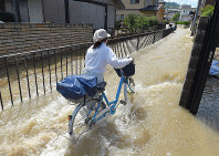 A woman pushes her bicycle down a street that has been turned into a river with a stronger current than the day before, in Hiroshima's Aki Ward, on July 9, 2018. (Mainichi)