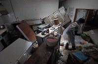 浸水し、泥まみれになった自宅を片付ける女性=岡山県倉敷市真備町地区で2018年7月9日午前11時56分、平川義之撮影