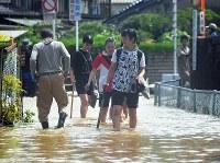 川の水が流れ込み、川のようになった道路を、スコップを手に歩く女子高生ら。友人宅の泥かきを手伝いに行くという。=広島市安芸区矢野西で2018年7月9日午前9時51分、手塚耕一郎撮影