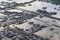 いまだに冠水した地域が残る真備町の市街地=岡山県倉敷市で2018年7月9日午前8時51分、本社ヘリから猪飼健史撮影