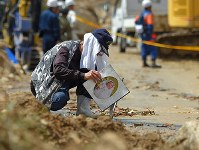 安否不明者の捜索が続く現場付近で、泥の中から見つかった写真を流れ出る水で洗う男性=広島県熊野町で2018年7月9日午後2時29分、手塚耕一郎撮影