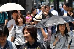 強い日差しが照りつける中、日傘を差して歩く人も=名古屋市中村区で2018年6月25日