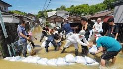 川の水が流れ込んだ住宅地で土のうを積む地域の住民=広島市安芸区矢野西で2018年7月9日午前10時28分、手塚耕一郎撮影