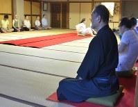 あぐらの状態で足を組み、座禅をする参加者=東京都台東区の全生庵で