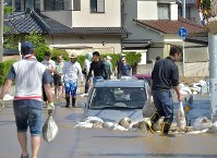 Residents clean up a road that became like a river due to flooding in Aki Ward in the city of Hiroshima on July 10, 2018. (Mainichi)