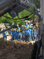 Police officers walk to a landslide site to search for missing people in the town of Kumano, Hiroshima Prefecture, on July 10, 2018. (Mainichi)
