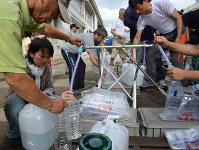 Disaster victims receive water at an evacuation site in the city of Kurashiki, Okayama Prefecture, on July 10, 2018. (Mainichi)