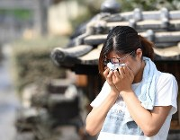 A woman weeps after seeing the status of her home, which was hit by a flood, in the city of Kurashiki, Okayama Prefecture, on July 9, 2018. (Mainichi)