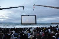 海に浮かぶスクリーンで上映を楽しむ「うみぞら映画祭」=兵庫県洲本市の大浜海水浴場で、村瀬優子撮影