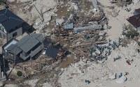 土砂に押し流された住宅地で捜索をする警察官ら=広島県坂町で2018年7月11日午前9時15分、本社ヘリから小出洋平撮影