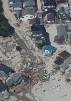 土砂に覆われた住宅地で捜索をする警察官ら=広島県坂町で2018年7月11日午前9時15分、本社ヘリから小出洋平撮影