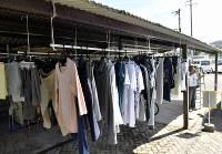 自転車置き場で避難者の洗濯物を干す場所を作る男性=広島県熊野町で2018年7月11日午前8時36分、藤井達也撮影