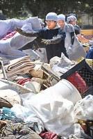 肱川の氾濫により出たゴミを車の荷台から下ろす人たち=愛媛県西予市で2018年7月11日午前10時27分、山崎一輝撮影