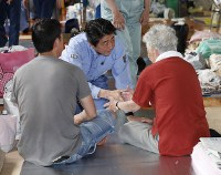 避難所を訪れ、被災者を激励する安倍晋三首相=岡山県倉敷市で2018年7月11日午前11時15分(代表撮影)