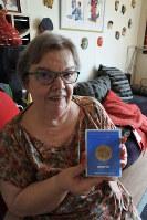 大阪万博の記念メダルを手にするマリークロードさん。お土産に買って大切にしているそう=2018年7月9日午後3時17分、久野華代撮影