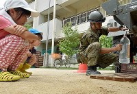 A Self-Defense Force member fills a bottle with water for children at a water supply point which was set up at Okada Elementary School in the Mabicho district in the city of Kurashiki, Okayama Prefecture, on July 11, 2018. (Mainichi)