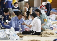 Prime Minister Shinzo Abe listens to a victim of the torrential rains at an evacuation center in the city of Kurashiki, Okayama Prefecture, on July 11, 2018. (Pool photo)