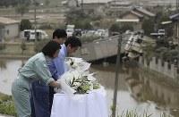 Prime Minister Shinzo Abe, center, offers flowers for victims of a flood in the Mabicho district of the city of Kurashiki, Okayama Prefecture, on July 11, 2018, with Kurashiki Mayor Kaori Ito, front, and Okayama Gov. Ryuta Ibaragi. (Pool photo)