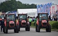 国際農業機械展の開会式で会場内を行進する無人トラクターの車列=北海道帯広市で2018年7月12日午前10時2分、鈴木斉撮影