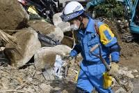 土砂の中から発見された写真を運ぶ警察官=広島県熊野町で2018年7月12日午前8時59分、藤井達也撮影