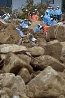 土砂崩れの被害が大きい地区で安否不明者の捜索を行う消防隊員たち=広島県熊野町で2018年7月12日午前8時25分、藤井達也撮影