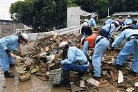 がれきを片付ける消防隊員ら=広島市安芸区矢野東で2018年7月12日午前6時55分、大西岳彦撮影