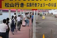 広島市内への道路や鉄道が寸断し、フェリー桟橋で長蛇の列を作る人たち。普段は通勤時間帯でも数人が利用するだけという=広島県呉市で2018年7月12日午前8時20分、三村政司撮影