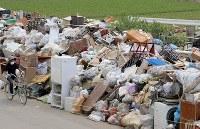 浸水被害を受け、使えなくなった家財道具などが至る所に積まれている。だめになった食料品なども混じり、周囲は生臭いにおいが漂っていた。近隣住民は「火事になったらどうしよう」と不安をにじませた=岡山県倉敷市真備町地区で2018年7月12日午前10時19分、平川義之撮影