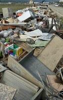 道路沿いに投棄され、積み上げられた家財道具など=岡山県倉敷市真備町地区で2018年7月12日午前8時46分、平川義之撮影