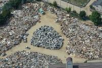 集められたゴミの山=広島県三原市で2018年7月12日午前9時37分、本社ヘリから加古信志撮影