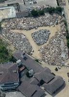 集められたゴミの山=広島県三原市で2018年7月12日午前9時35分、本社ヘリから加古信志撮影