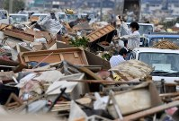 浸水被害で使えなくなった家財道具などを捨てる人たち=岡山県倉敷市真備町地区で2018年7月12日午後1時49分、猪飼健史撮影