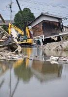 被害の大きかった真備町では重機を使ってがれきが撤去されたいた=岡山県倉敷市真備町地区で2018年7月12日午後2時20分、猪飼健史撮影