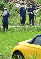 亡くなった入江善彦さんが乗っていた車を見つめる愛媛県立野村高校女子バスケ部の部員たち=愛媛県西予市で2018年7月12日午前10時37分、山崎一輝撮影