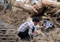 土砂崩れの現場で、思い出の品などを探す男性=広島県熊野町で2018年7月12日午後5時21分、小川昌宏撮影