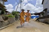 泥が乾燥し、土ぼこりが舞い上がるのを防ぐために水をまく消防隊=広島県熊野町で2018年7月12日午前11時38分、藤井達也撮影