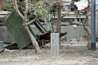 川辺小学校の運動場には1976年(昭和51年)の台風17号で浸水した際の水位を示す石柱がある。辺りにはどこからか流れてきた物が散乱していた=岡山県倉敷市真備町地区で2018年7月12日午後3時5分、平川義之撮影