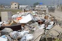 道路沿いに投棄され、積み上げられた家財道具など=岡山県倉敷市真備町地区で2018年7月12日午前8時42分、平川義之撮影
