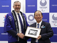 Etienne Thobois, left, Paris 2024 director general and Toshiro Muto, right, Tokyo 2020 CEO pose together during the signing ceremony of the memorandum of understanding on the relations and cooperation between the two organizing committees in Tokyo, on  July 11, 2018. (AP Photo/Shuji Kajiyama)