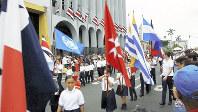 映画「コスタリカの奇跡」のワンシーン。国連旗や各国の国旗を持ってパレードする子どもたち=上映サポートの会「プラ・ヴィダ!」提供。上映日程は同会事務局(03・5802・3121)へ
